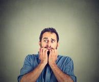 Тревоженый молодой человек сдерживая его пальцы ногтей freaking вне Стоковая Фотография RF