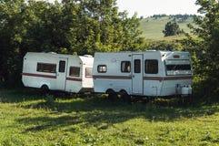 Трейлер каравана располагаясь лагерем на зеленой лужайке под деревом в весеннем времени Стоковые Изображения