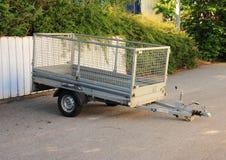 Трейлер с сетью металла припарковал на белой загородке Стоковая Фотография RF
