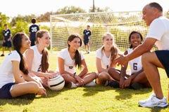Тренер давая беседу команды к женской футбольной команде средней школы Стоковые Фотографии RF