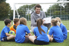 Тренер давая беседу команды к футбольной команде начальной школы стоковое фото rf
