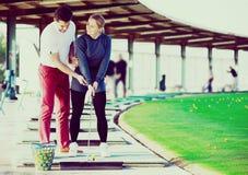 Тренер гольфа учит игре женщины Стоковые Изображения