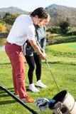 Тренер гольфа учит игре женщины Стоковое фото RF