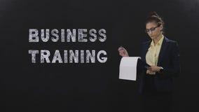 Тренер дела женщины с положением папки документов на черной предпосылке сток-видео