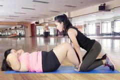 Тренер женщина помощи тучная для делать сидит поднимает Стоковое Изображение