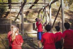 Тренер инструктируя детей в лагере ботинка Стоковые Фотографии RF