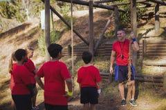 Тренер инструктируя детей в лагере ботинка Стоковые Изображения RF