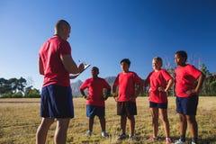 Тренер инструктируя детей в лагере ботинка Стоковые Изображения