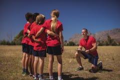 Тренер инструктируя детей в лагере ботинка Стоковое Фото