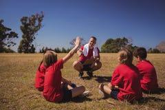 Тренер инструктируя детей в лагере ботинка Стоковое Изображение RF