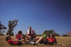 Тренер инструктируя детей пока работающ в лагере ботинка Стоковое фото RF