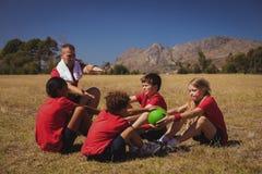 Тренер инструктируя детей пока работающ в лагере ботинка Стоковая Фотография RF