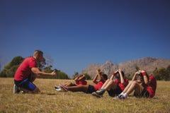 Тренер инструктируя детей пока работающ в лагере ботинка Стоковое Фото