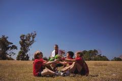 Тренер инструктируя детей пока работающ в лагере ботинка Стоковое Изображение