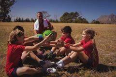 Тренер инструктируя детей пока работающ в лагере ботинка Стоковые Изображения