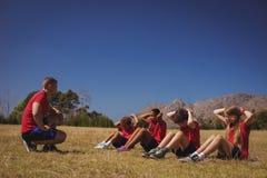 Тренер инструктируя детей пока работающ в лагере ботинка Стоковая Фотография