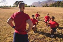 Тренер инструктируя детей пока работающ в лагере ботинка Стоковые Изображения RF