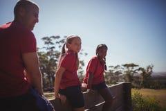 Тренер и девушки сидя совместно на деревянной стене Стоковое Изображение