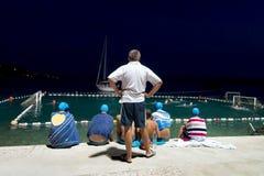 Тренер и игроки водного поло наблюдая спичку Omis Стоковое Изображение
