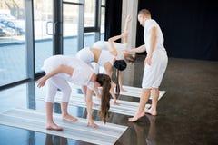 Тренер и молодые женщины практикуя йогу на циновках Стоковое Изображение RF