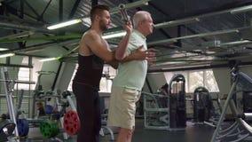 Тренер контролирует тренировки старшего клиента стоковые фотографии rf