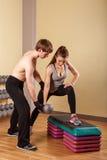 Тренер объясняет тренировку девушки с гантелями Стоковое Изображение
