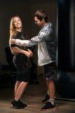 Тренер помогает белокурой девушке в костюме EMS подготовить для тренировки Стоковое Изображение RF