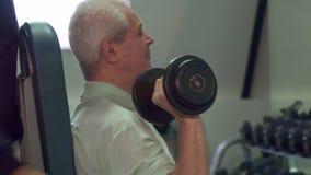 Тренер помогает старшему клиенту во время тренировки стоковые изображения