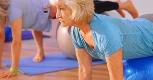 Тренер помогая старшей женщине в выполнять йогу 4k видеоматериал