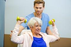 Тренер помогая старшей женщине поднять гантели в студии фитнеса Стоковые Фотографии RF