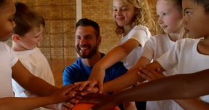Тренер по баскетболу и schoolkids формируя стог руки в баскетбольной площадке 4k видеоматериал