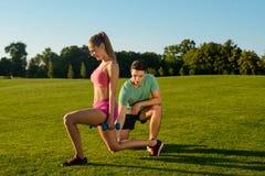 Тренер приниманнсяый за фитнес с девушкой на природе Стоковая Фотография RF