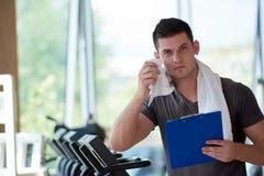 Тренер при доска сзажимом для бумаги стоя в ярком спортзале Стоковое Изображение