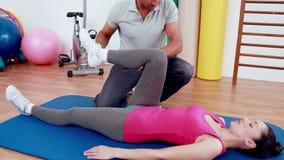 Тренер работая с женщиной на циновке тренировки видеоматериал