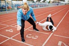 Тренер спорта волоча вымотанного толстенького клиента к линии отделки стоковые фотографии rf