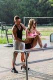 Тренер фитнеса помогая привлекательной женщине Стоковая Фотография