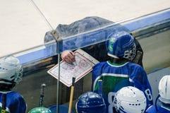 Тренер хоккейной команды ребенка объясняет план игры Стоковые Изображения RF