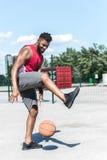 Тренировка баскетболиста с шариком баскетбола на суде Стоковые Изображения