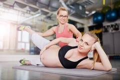 Тренировка беременной женщины на спортзале с личным тренером Стоковые Фотографии RF