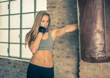 Тренировка бойца женщина пробивая сумку бокса тяжелую Стоковое Изображение