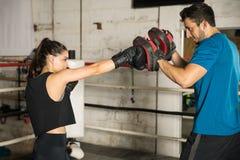 Тренировка боксера с ее тренером Стоковые Изображения