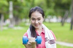 Тренировка веса гантели женщины фитнеса поднимаясь снаружи Стоковые Изображения RF