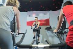 Тренировка времени положительных женщин различная на велотренажерах стоковые изображения rf