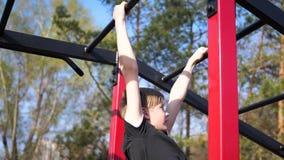 Тренировка в свежем воздухе Молодой сильный парень делая тренировки на баре Парк осени сток-видео