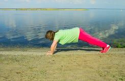 Тренировка женщины на речном береге Стоковое фото RF