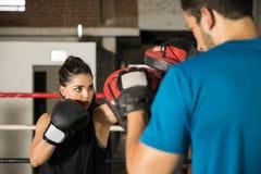 Тренировка женщины с перчатками бокса Стоковая Фотография