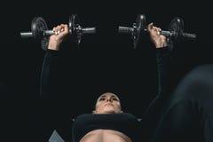 Тренировка женщины фитнеса с гантелями и лежать изолированный на черноте Стоковая Фотография