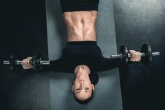 Тренировка женщины фитнеса с гантелями и лежать на циновке Стоковое Изображение RF