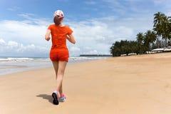 Тренировка женщины jogging на пляже в каникулах стоковая фотография rf