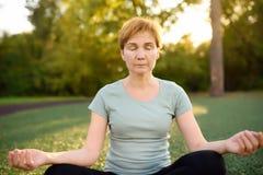 Тренировка или размышлять йоги зрелой женщины практикуя на открытом воздухе стоковая фотография